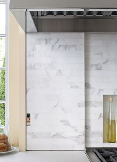 """A sliding marble backsplash on the range wall conceals a small television and bottles of oils and spices. """"They wanted some edge to the design—some snap, without being over the top,"""" says kitchen designer Mick De Giulio. Stove Backsplash, Backsplash Panels, House Arch Design, Door Design, A Thoughtful Place, Basement Inspiration, Kitchen And Bath, Kitchen Oven, Kitchen Hoods"""