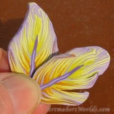 Violet edged yellow feather polymer clay cane