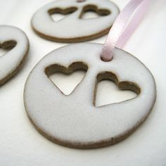 Ceramic heart decorations (white)    These delicate little ceramic heart decorations are handmade from stoneware and glazed in a gloss white glaze.    Measures about 35mm across.