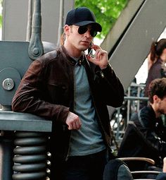 He looks so cool talking on the phone in those shades and that cap.