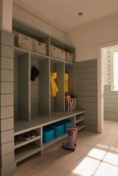 Perfect mud rum with custom built-in cubbies, wicker baskets,  and olive shiplap on the walls   Weitzman Halpern