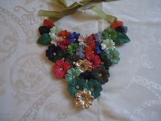 Maxi colar confeccionada com flores e flohas  de couro em varias cores. As flores tem em seu miolo um stras transparente. Fecho em fita de cetim verde. R$113,90