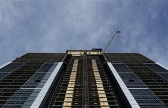 The boom of tower crane operator George DeFreitas' crane peeks out from the top of the 42 story Couture condo in Toronto, Tuesday afternoon, April 17, 2012.