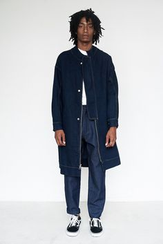 Eckhaus Latta Denim Flasher Coat - Knee length coat with front two-way zip and external fly guard with hidden shank closure - Drop waist welt pockets on front of body. Exaggerated gusset in sleeve wit
