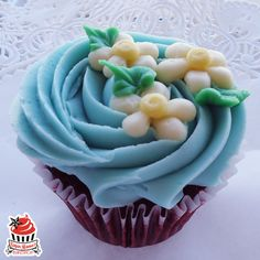 Red velvet cupcake topped with a beautiful swirl of blue cream cheese frosting and little buttercream flowers. A sweet little Easter surprise beautiful for any springtime occasion.