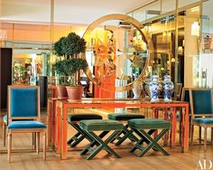 In another reception area, the company logo, emblazoned in brass against a mirrored expanse, hangs above a grouping of furnishings also used at the label's boutiques.
