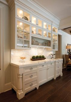 Stunning kitchen with white cabinetry featuring turned wood accents pairing with polished nickel hardware alongside marble countertops and a seamless marble backsplash.