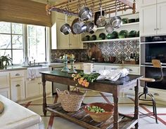 This interesting, eclectic kitchen has a multitude of unusual elements.  The rather simple cabinetry and rustic island paired with the rather ornate, colorful backsplash.  The somewhat modern looking barstool with the country details on the island and simple pot rack hanging above gives the space character.  And the diagonal wood and marble floor lend a fun, unexpected twist.  eclectic « Sheri Martin Interiors