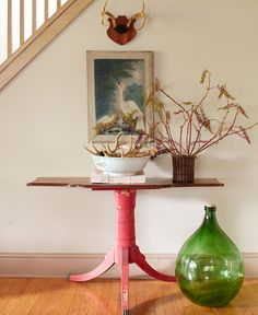 A rosewood vase and brown transferware bowl display pokeweed branches and antlers, respectively, on the entryway table. The oversize green bottle hails from an area flea market. The wall is painted Sycamore Green by Restoration Hardware.   - HouseBeautiful.com