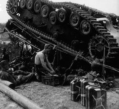 Wounded troops seek cover behind a destroyed German Panzer IV tank. Overturned by bomb attacks from Allied planes. Avranches area, Aug 1944.