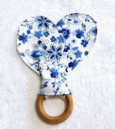 Vintage Blue Floral Bunny Ears Teething Ring. A beautiful vintage blue floral teether toy for a very special baby. The ring is a 2.5 inch Maple Hardwood sealed in 100% Pure Beeswax and Organic Olive oil for a smooth finish that soothes baby's gums. Care: The teething ring is removable for washing the bunny ears or changing the teething ring. Wash ring by hand with a warm cloth. Front bunny ear fabric is 100% cotton flannel, back side of bunny ears is a white organic cotton.