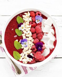 Learn how to make one of these easy, healthy and totally vegan smoothie bowl recipes and your breakfast will never be the same—this banana, blackberry, blueberry, peach and coconut water bowl is loaded with toppings like raspberries, raw cashews, shredded coconut, mint and edible flowers!