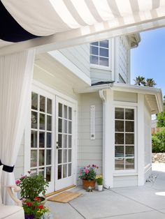 A shaded pergola is located right next to this Cape Cod-style house. The house's style is complemented by the East Coast touches throughout the backyard patio, including comfy, casual furnishings and pops of blue.