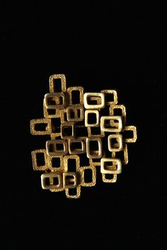 1960s 1970s Coro abstract geometrical modern goldtone brooch composed of two layers of hollowed rectangular and square elements. The elements composing