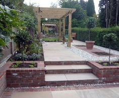 I like the pergola with climbers, and the height of the steps and raised beds give some interest and zone the areas. Not enough grass though. Sunken Patio, Sunken Garden, Sloped Garden, Brick Garden Edging, Garden Paving, Terrace Garden, Raised Patio, Raised Beds, Back Gardens