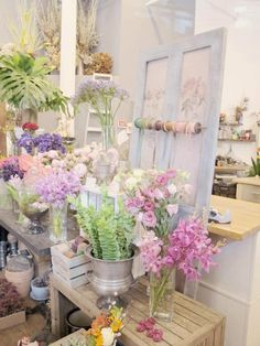 Fresh pastel flower shop. The shabby chic door and ribbon roll is a cute idea.