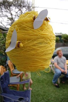 "Bee Pinata... Wrap a round pinata in yellow yarn and display a few bees on the ""hive""... if you don't want to do a pinata, then you could cover balloons or styrofoam or something of the shape and hang around as decor.."