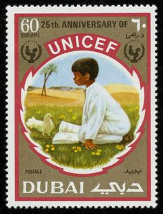 A 1971 postage stamp from Dubai commemorates UNICEF's 25th anniversary. It shows a boy kneeling in a meadow in front of an open book and a dove. © UNICEF/NYHQ2006-2321/. Courtesy of Fouad Kronfol