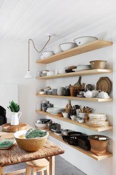 open kitchen storage with vintage crockery, wooden utensils, and chopping blocks