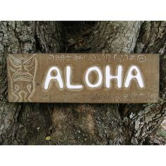 """A hand made wooden """"ALOHA"""" welcome sign with a antique rustic finish, featuring some petroglyph carvings as well as a carved Tiki on the side. This very tropical piece measures 24 inches long by 7 inches tall."""