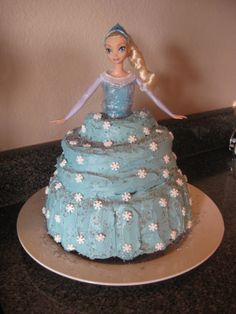 """Disney Frozen Elsa doll birthday cake-- Wrap Barbie in plastic wrap.  Use 2 cake mixes, bundt cake on bottom (filled w/batter as high as possible in pan), layer top w/pieces cut from 8-9"""" circle pan and/or cupcake size.  Before frosting, freeze cake several hours to avoid crumbs/breakage."""