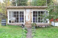 A greenhouse made from reclaimed wood and old windows
