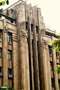 ❤ - Art Deco building in Mumbai, India with two elongated statues flanking the door. They are armed and dangerous.