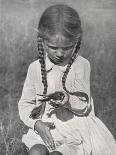 A little girl, with long braided hair, sitting in a field and holding a swallow in her hand.