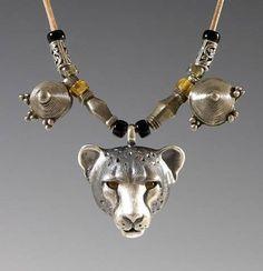 Totem necklace: Silver cheetah w/ smoky quartz eyes, Telsum and Tuareg beads.