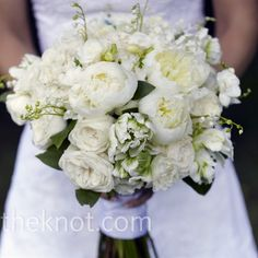 bouquet of white hydrangeas, garden roses, peonies, freesia, and lily of the valley with parrot tulips.
