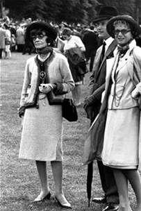 Coco Chanel con el traje sastre que lanzó en 1954. Chnel matuvo el sobrero, los guantes y los zapatos, y la postura de adelantar ls cederas. Sin embargo, cambió la silueta.