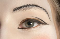 A stitched brow and shapely gold and black liner eye at  Vivienne Westwood RTW S/S 2011 #makeup