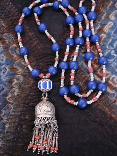 by Luda Hunter | Necklace; an antique 6-layer Chevron glass bead and an old Afghan silver domed pendant with chain and coral dangles are combined with Antique African gooseberries - the tiny precious and rare white striped trade beads, old coral glass trade beads, tiny Ethiopian metal spacers and old Indonesian cobalt blue glass beads.  {310$AUD}