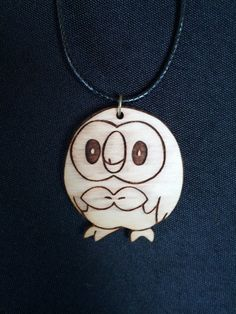 This listing is for one Rowlet wooden engraved necklace on black cord