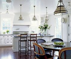 white kitchen + black/gray counters + dark wood table and blue bistro chairs