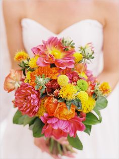 bright pink and yellow bouquet of dahlias, mums, craspedia, carthamus and ranunculus
