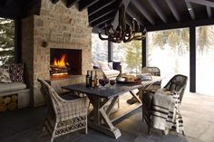 The large stone fireplace and walls of windows make this patio area a dreamy gathering place for après-ski dining and drinking. M. Elle created the Sun Valley, Idaho, space, which features a rustic chandelier and a set of wicker dining chairs around the farm-style table.