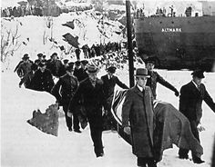 Flag-draped coffins containing German dead are brought ashore for burial after the Altmark Incident in Jøssingfjord, Norway, 16 February 1940