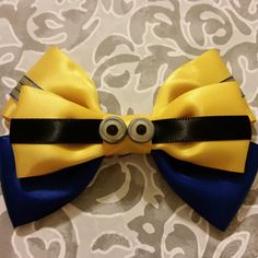 Own your very own minion! Despicable Me character hair bow. The eyes are hand made out of polymer clay. The bow is made of satin and sheer ribbon and