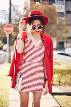 Red and white outfit in a preppy inspiration. Wearing striped dress with white shirt and red coat. Accessories with red hat, Carel shoes and hat.