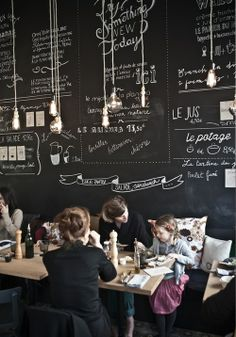 // cafe section, large chalk board in frame with roasts, teas pastry prices