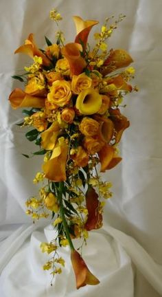 Orange and yellow cascading bouquet with roses and calla lilies. Orange ranunculus, carnations tulips and lily grass would be added