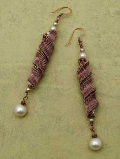 In these earrings by Sandra Lupo, a woven wire ribbon twists around a core of coiled pearls.