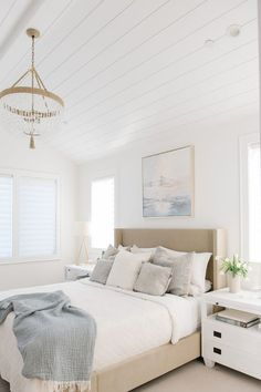 A clear beaded chandelier hangs from a vaulted shiplap ceiling over a beige wingback bed dressed in white bedding topped with white and gray pillows placed beneath an art piece. Bedroom Ceiling, Bedroom Decor, Master Bedroom Chandelier, Design Bedroom, Beige Headboard, Apartment Decoration, Shiplap Ceiling, How To Dress A Bed, White Shiplap
