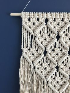 This item is made to order and will be ready for shipping in 3-5 business days.  Macrame wall hanging made with 5mm white cotton cord. This wall hanging is off-white and will add the perfect boho vibe to any gallery wall, bedroom, nursery, or living room. Measures approximately 12 inches wide and 21 inches long at its longest point including the fringe. Wood dowel is 15 inches wide and is included.  If you have any questions, feel free to contact me. Check out my other wall hangings here…