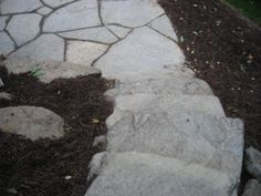 """Rustic, natural, top-rock boulder steps leading to an irregular flagstone patio space.  We hand select boulders that have a nice flat top and have the right thickness (6"""" - 8"""") to serve as a comfortable step. These boulders are top rock meaning they have thousands of years of weathering, giving them a cool, more natural look and lots of individual character; as opposed to boulders that have been dug out of the ground that tend to be more yellow and harsh."""