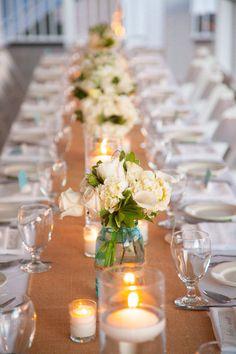 burlap table runner w/ silver mason jars with burgundy sun flowers, cinnamon stick tea light votives & scattered red rose petals