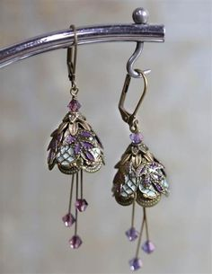Embellished blossom earrings recall 19th century illustrations of tiny fairy petticoats. Tiers of latticed brass give way to radiant purple crystals.