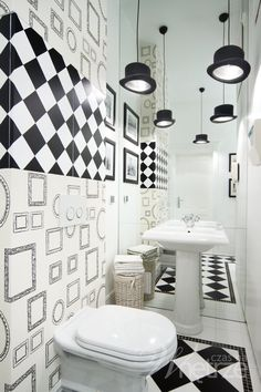 Black and white Eijffinger wallpaper in the bathroom, frames, checker board and bowler hat lights. Alice in Wonderland?