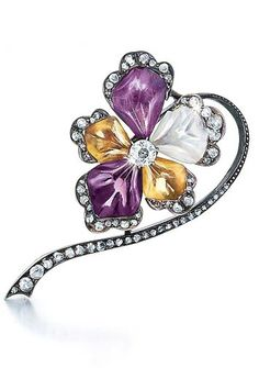 An Antique Victorian Colored Stone and Diamond Flower Brooch Silver over 18k gold, formed as a flower with five petals of carved amethyst, citrine and rock crystal, the tips and stem set with small rose cut diamonds, centered with an Old European cut diamond (approximately 0.40ct, mounted weight established by formula). Circa 1890
